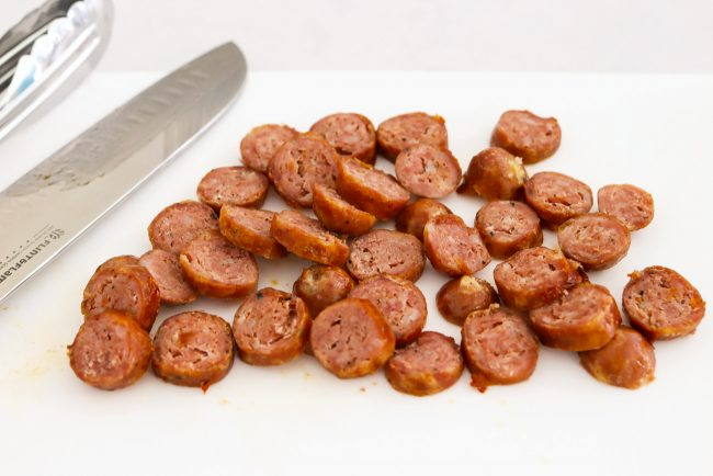 Sliced rounds of cooked sausage on a chopping board with a knife and tongs.