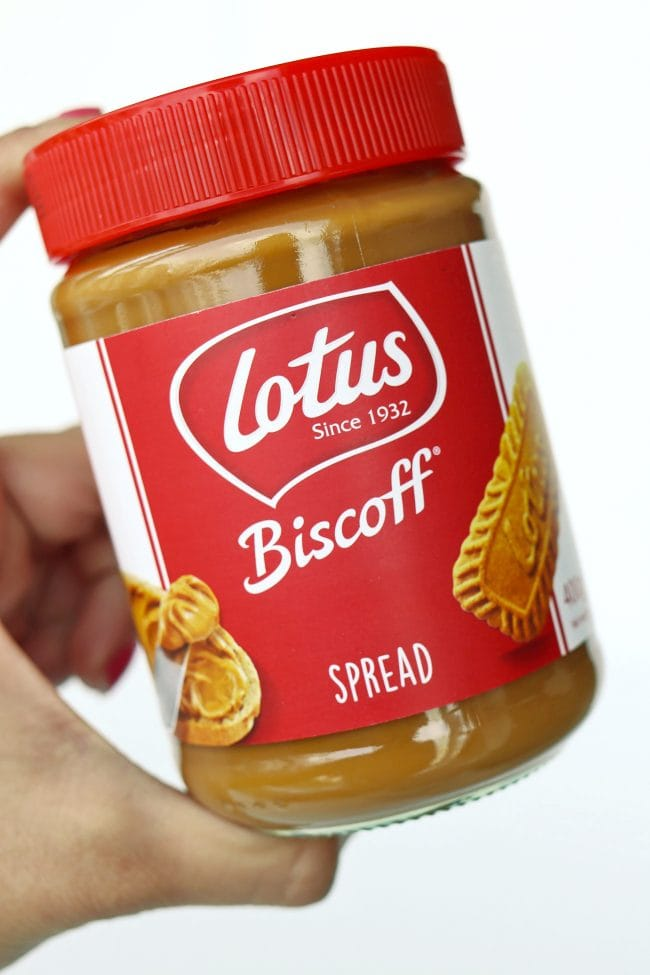 Hand holding up a jar of Lotus Biscoff Creamy Cookie Butter Spread.