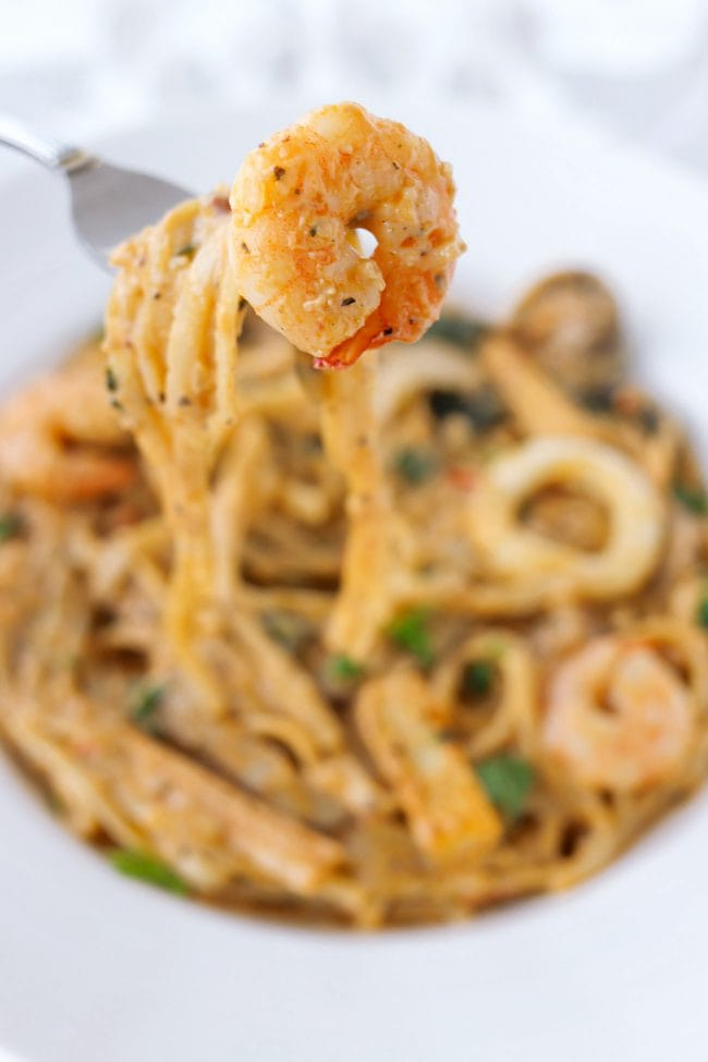Hand holding up a fork with a piece of shrimp and pasta above plate with pasta and seafood.
