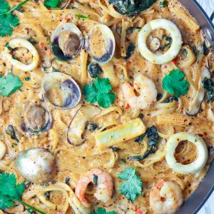 Creamy Tom Yum Pasta with clams, shrimp, squid, spinach, baby corn, mushrooms, and chopped coriander in a large black pan