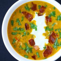 Pumpkin Chicken Soup garnished with chopped coriander, yogurt, and crispy bacon pieces in a white round bowl.