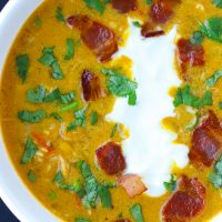 Pumpkin Chicken Soup in bowl with crispy bacon pieces, yogurt, chopped coriander.