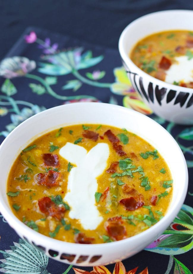 Two diagonally placed bowls of soup garnished with chopped coriander, yogurt, and crispy bacon pieces.