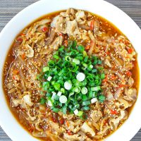 Japanese sauce pork in serving bowl topped with white sesame seeds and chopped spring onion.