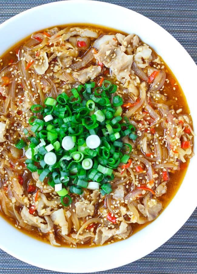 Japanese sauce pork in white round serving bowl topped with white sesame seeds and chopped spring onion.