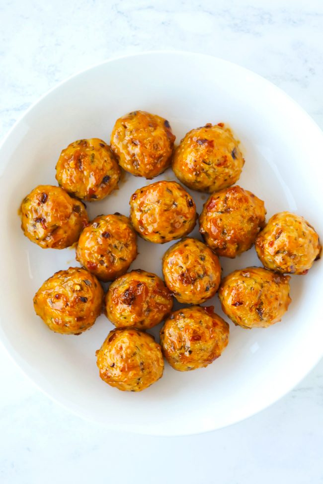 Chicken meatballs on a white round plate coated in sweet chili peanut sauce.