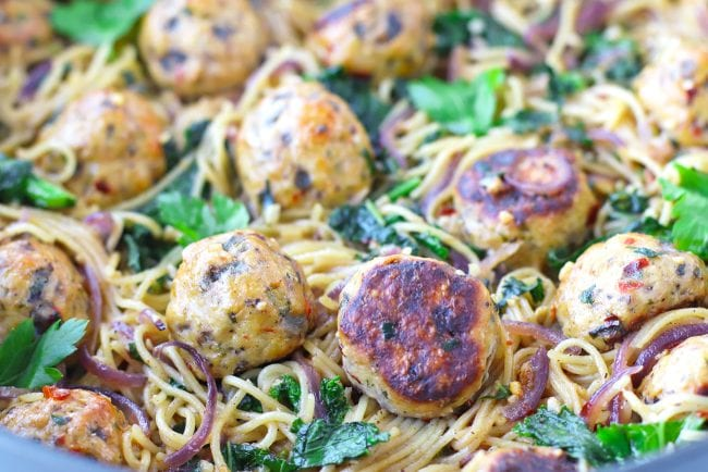 Deep large sauté pan with Brown Butter Miso Pasta and Baked Spicy Chicken Meatballs garnished with fresh parsley leaves.