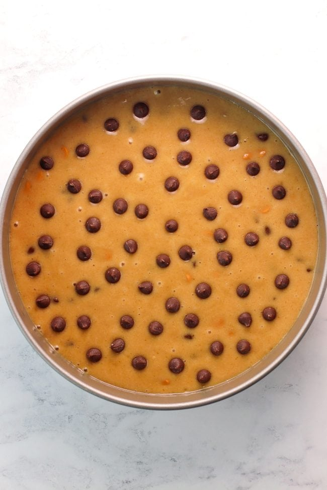 Unbaked cookie cake batter in a round 8-inch baking pan and dotted with chocolate chips.