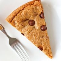 Chocolate Chip & Butterscotch Chip Cookie Cake slice on a white round plate with a fork next to it.