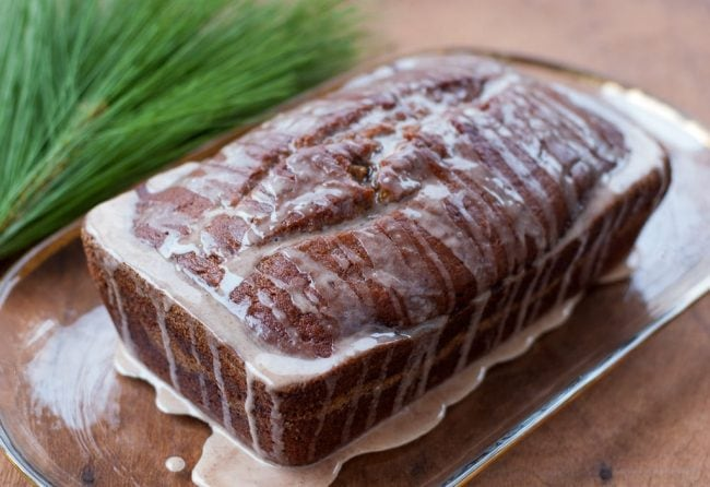Pumpkin Banana Bread loaf topped with cinnamon glaze on a rectangular long glass plate with rounded corners.