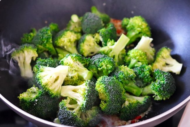 Broccoli florets with garlic and chopped red chiles in a wok with smoke coming out.