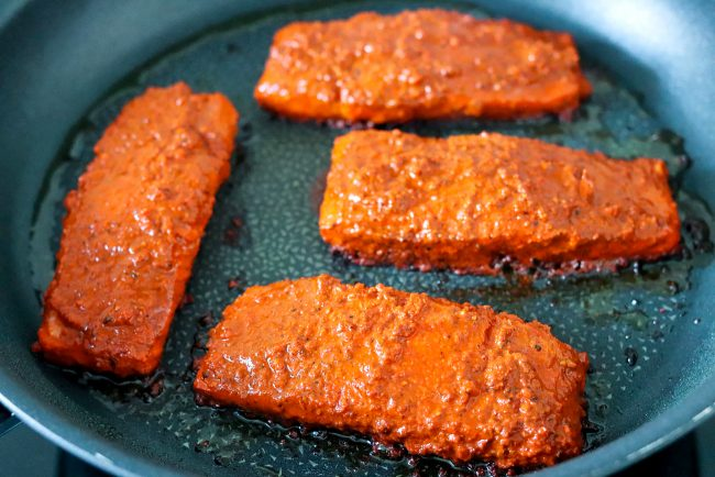 Four salmon fillets coated in an orange-red spicy paste marinade pan-frying skin side down in a large nonstick skillet on the stovetop.