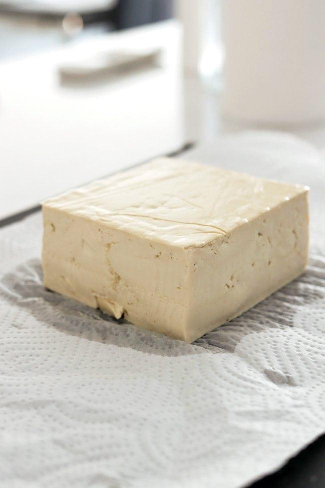 Tofu block on paper towel on top of black cutting board on countertop.