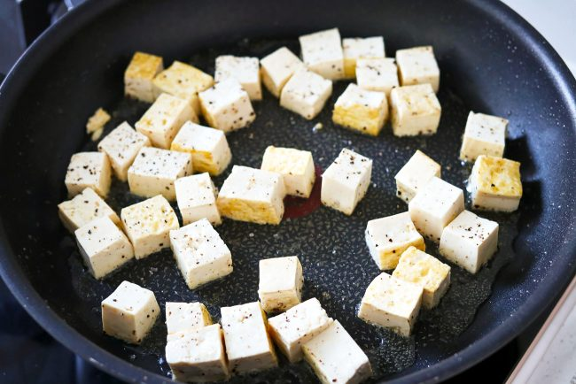 Salt and pepper seasoned tofu cubes crisping up in a black nonstick skillet with a bit of oil.