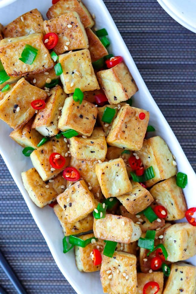 Close-up top view of a plate with pan-fried tofu cubes garnished with chopped spring onion, red chili, and toasted white sesame seeds.
