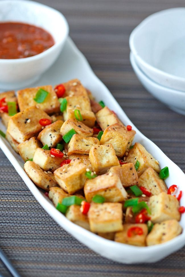 Front view of a long white plate with a bowl of spicy dipping sauce and crispy pan-fried tofu cubes sprinkled with chopped spring onion, chopped red chili, and toasted white sesame seeds. Small plates on right side of the plate with tofu.
