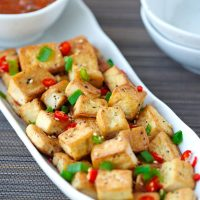 Front view of a long white plate with a bowl of spicy dipping sauce and pan-fried tofu cubes sprinkled with chopped spring onion, chopped red chili, and toasted white sesame seeds. Black chopsticks and small plates on either side of the plate.
