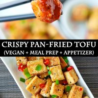 Black chopsticks holding up a fried tofu cube that's been dipped in a spicy orange sauce, and a plate with pan-fried tofu cubes sprinkled with chopped spring onion, chopped red chili, and toasted white sesame seeds.