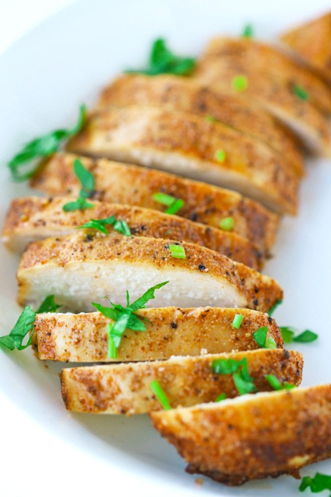 Close up of a seasoned and baked sliced chicken breast that's fanned out in a white round plate and garnished with fresh chopped parsley.