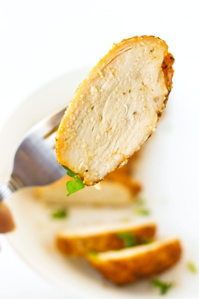Fork holding up a piece of chicken above a plate with a sliced baked chicken breast that is garnished with chopped fresh parsley.
