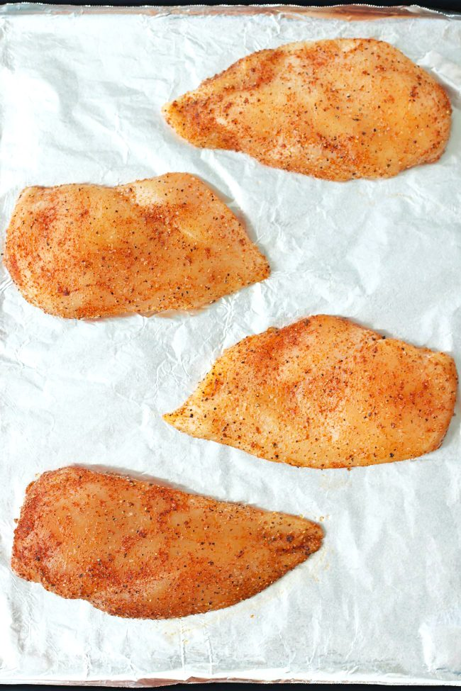 Four uncooked seasoned chicken breasts on a foil lined baking tray.