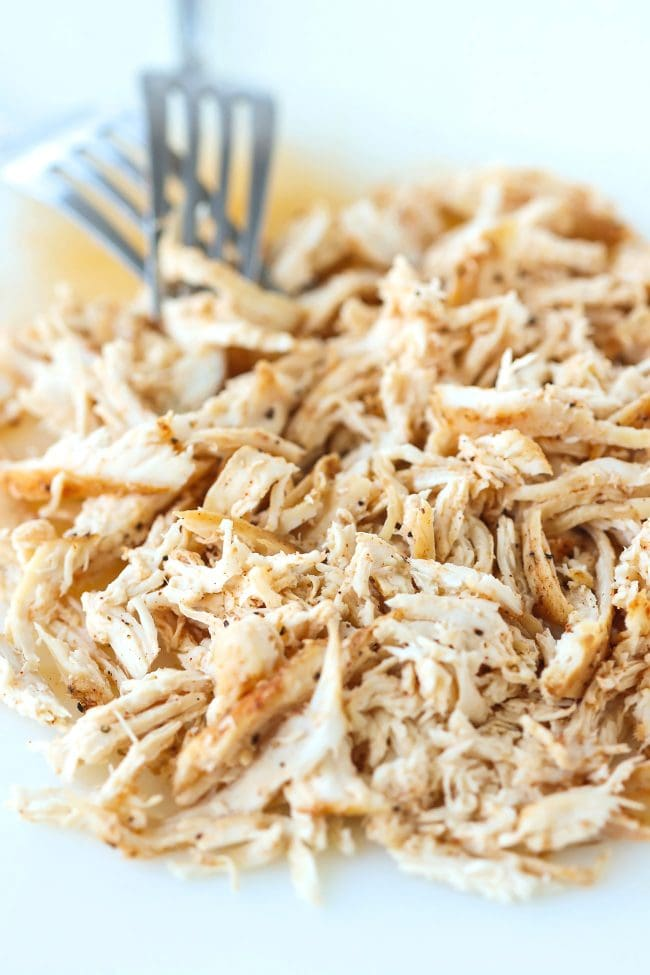 Shredded chicken on a chopping board with two silver forks.