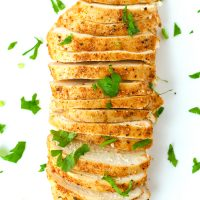 Thinly sliced seasoned and baked chicken breast garnished with fresh chopped parsley.
