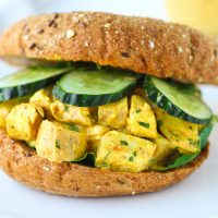 A Mango Chicken Salad Bagel Sandwich with mixed salad greens and cucumber slices on a white plate.