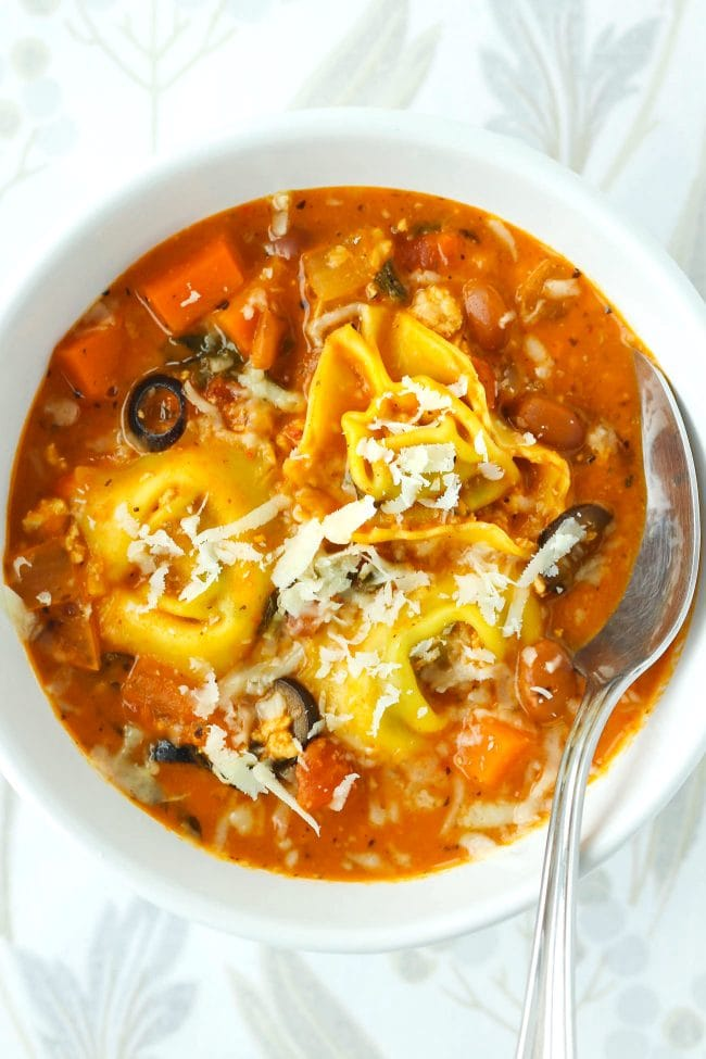 Tomato basil tortellini soup with pinto beans, chicken, diced carrot, and sliced black olives topped with grated cheese in a white round bowl with a silver spoon.