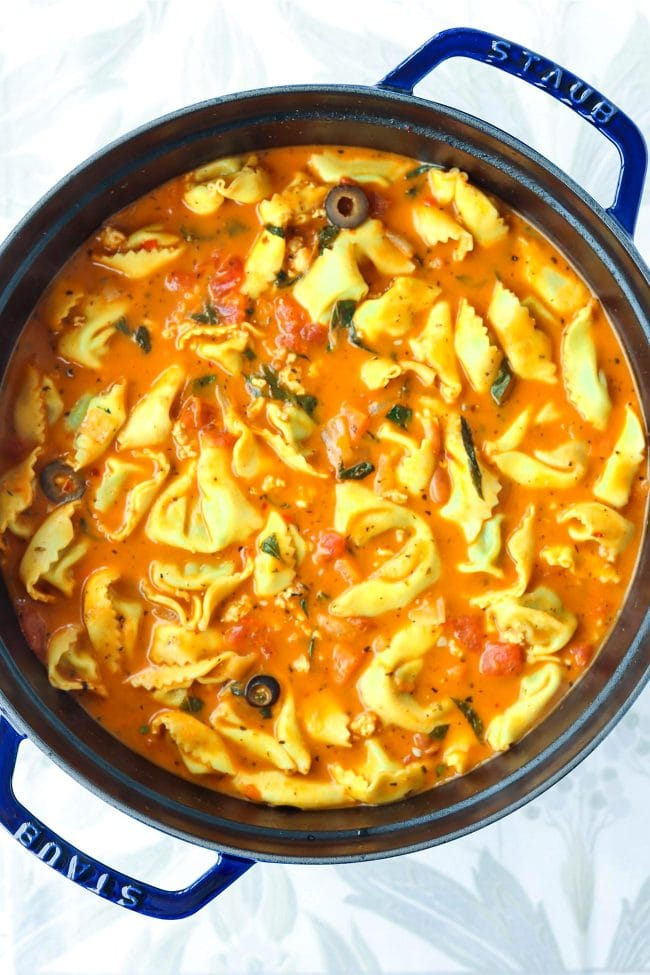 Creamy tomato basil tortellini soup in a blue Dutch oven on top of a floral grey napkin.