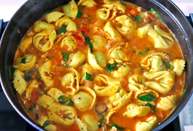 Creamy tomato soup with tortellini, ground chicken, sliced black olives, and fresh basil leaves simmering in a Dutch oven on the stovetop.