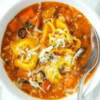 Tomato basil tortellini soup with beans, ground chicken, diced carrot, and sliced black olives topped with grated cheese in a white round bowl with a silver spoon.