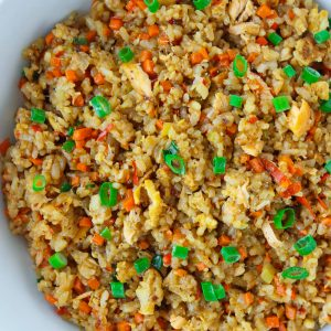 Salmon and egg fried rice with carrots, spring onion, and black pepper in a white round serving bowl.