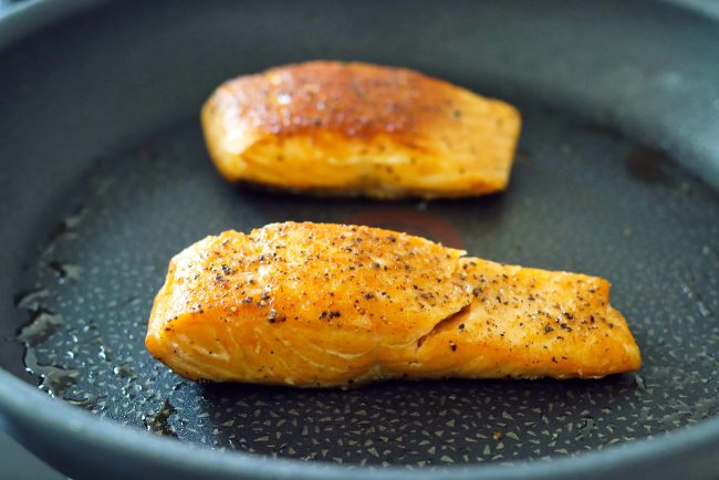 Two black pepper and salt seasoned salmon fillets pan-frying in a skillet with oil.