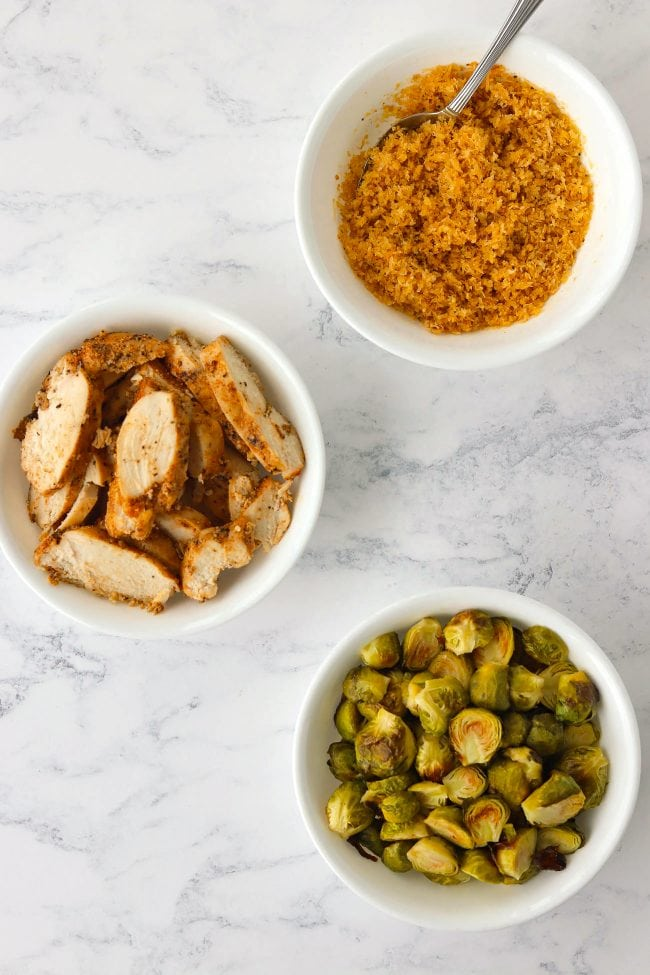 Three white bowls with breadcrumbs topping and a spoon, baked seasoned chicken breast slices, and roasted brussels sprouts.