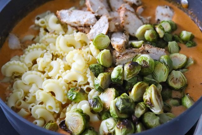 Unmixed pasta, roasted brussels sprouts, and chicken slices in a large black deep sauté pan with creamy spicy orange cheese sauce.