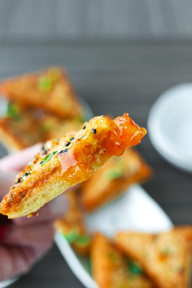 Hand holding up a prawn toast piece dipped in Thai Sweet Chili Sauce.