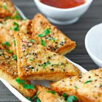 Prawn Toast triangles on a long plate garnished with chopped coriander and served with a small bowl of Thai Sweet Chili Sauce on the side.