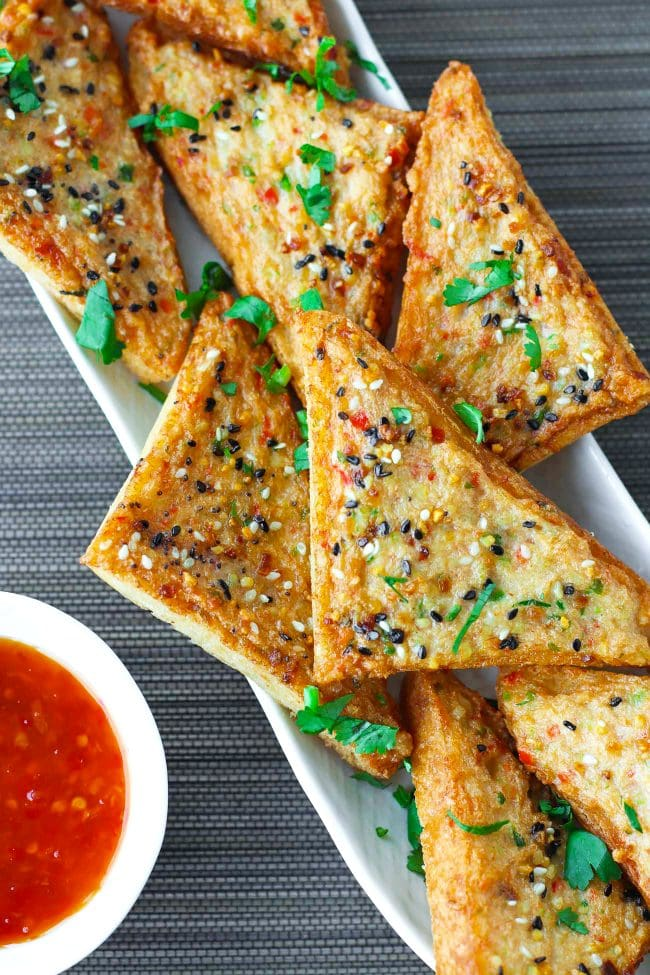 Prawn Toast triangles on a long white plate garnished with chopped coriander and served with a small bowl of Thai Sweet Chili Sauce on the side.
