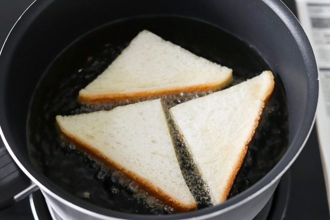 Three bread triangles frying in a pot of bubbling oil on the stovetop.