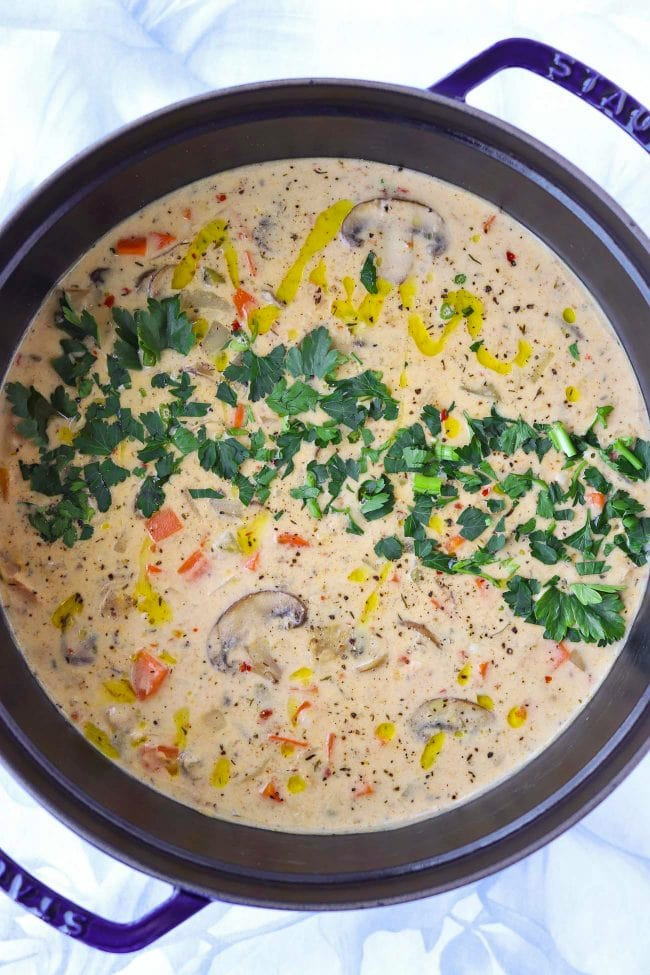 Blue Dutch oven with creamy soup with mushroom, chicken, carrots, celery, and garnished with parsley leaves and a drizzle of extra virgin olive oil.