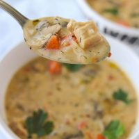 Spoonful of cream soup with mushroom, chicken, carrot and rice being held above a bowl with creamy mushroom and veggie soup and garnished with parsley leaves.