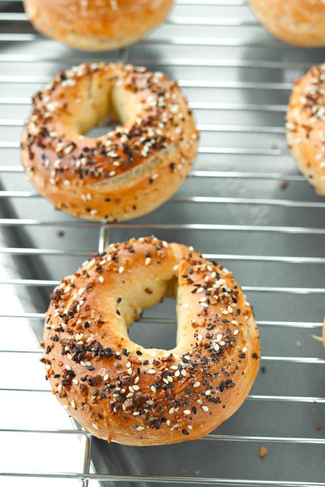 Everything bagels on a cooling rack on top of a baking tray.