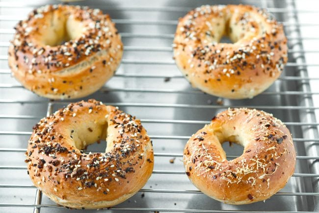 Two grated cheese bagels, three everything bagels, and a crushed red pepper and cheese bagel on a cooling rack on top of a baking tray.