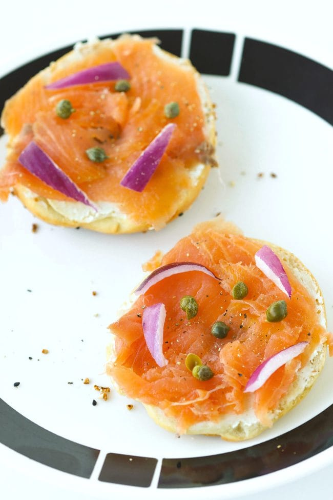 Bagel halves topped with cream cheese, smoked salmon, red onion slices, capers, and black pepper on a white and black plate.