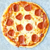 A freshly baked whole pepperoni pizza on a parchment paper lined baking tray.