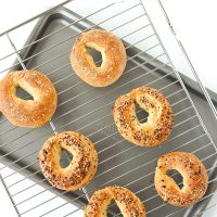 Two cheese bagels, three everything bagels, and a cheese and crushed red pepper bagel on a cooling rack on top of a baking tray.