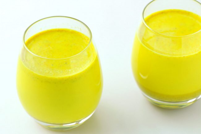 Two drink glasses with yellow turmeric milk with spices.