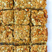 Apricot almond square shaped oat slices on parchment paper.