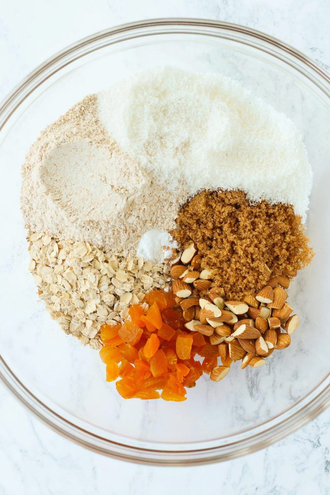 Wholegrain wheat flour, desiccated coconuts, old fashioned rolled oats, light brown sugar, chopped almonds, chopped dried apricots, and baking soda in a large mixing bowl.